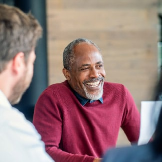 man smiling while in a meeting